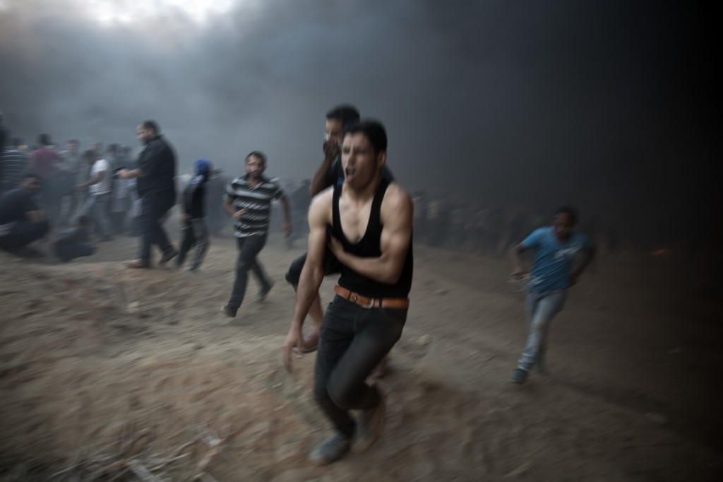 A wounded Palestinian protester runs out towards the ambulances during a protest at the Gaza Strip's border with Israel, Friday, Oct. 12, 2018. (AP Ph