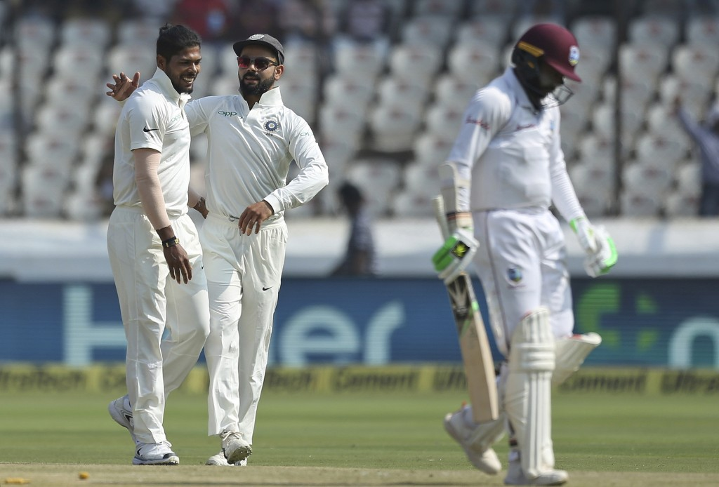 Indian bowler Umesh Yadav, left, celebrates the dismissal of West Indies' cricketer Devender Bishoo during the second day of the second cricket test m