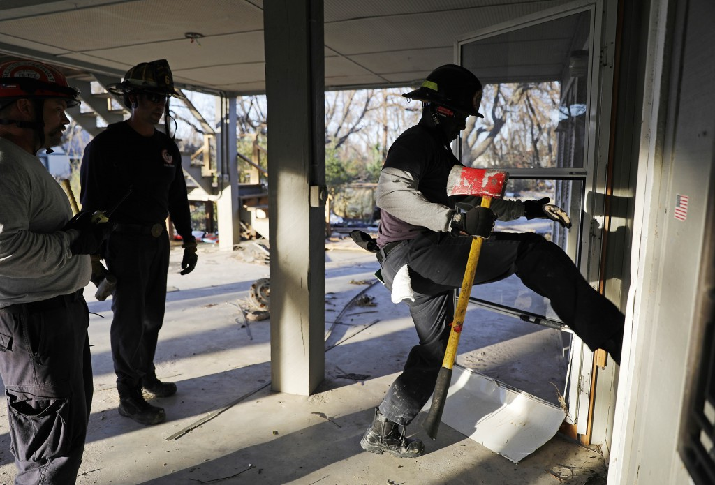 Members of a South Florida urban search and rescue team try to gain entry to a home while looking for survivors of hurricane Michael in Mexico Beach,