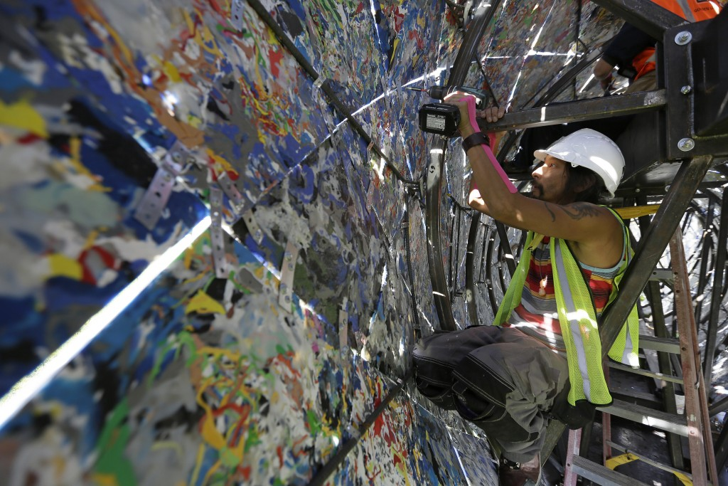 Jared Chen works at reinforcing panels inside a blue whale art piece made from discarded single-use plastic at Crissy Field Friday, Oct. 12, 2018, in