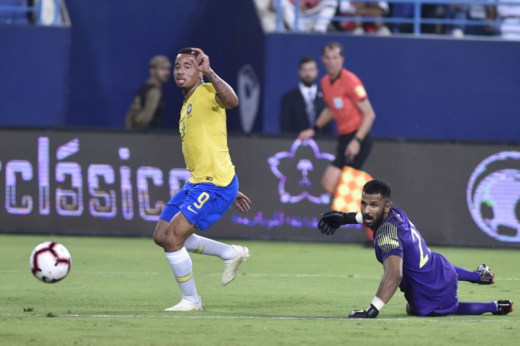 Brazil's Gabriel Jesus, left, scores his side's opening goal against Saudi Arabia goalkeeper Mohammed Alowais during a friendly soccer match between B