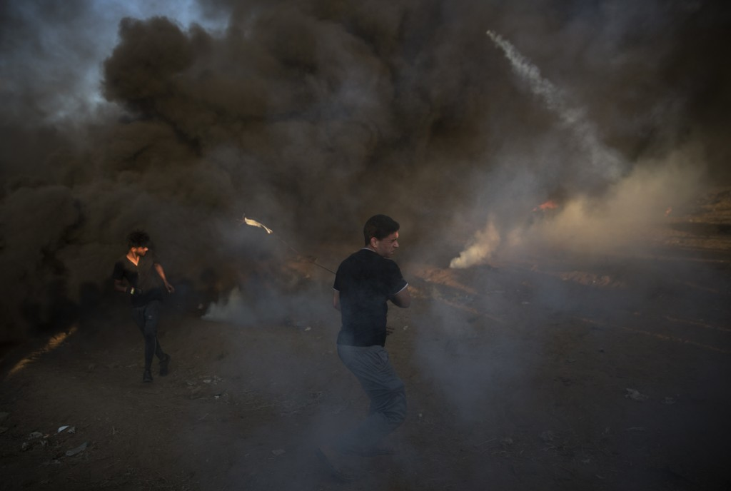 Palestinian protesters run for cover from teargas fired by Israeli troops during a protest at the Gaza Strip's border with Israel, Friday, Oct. 12, 20