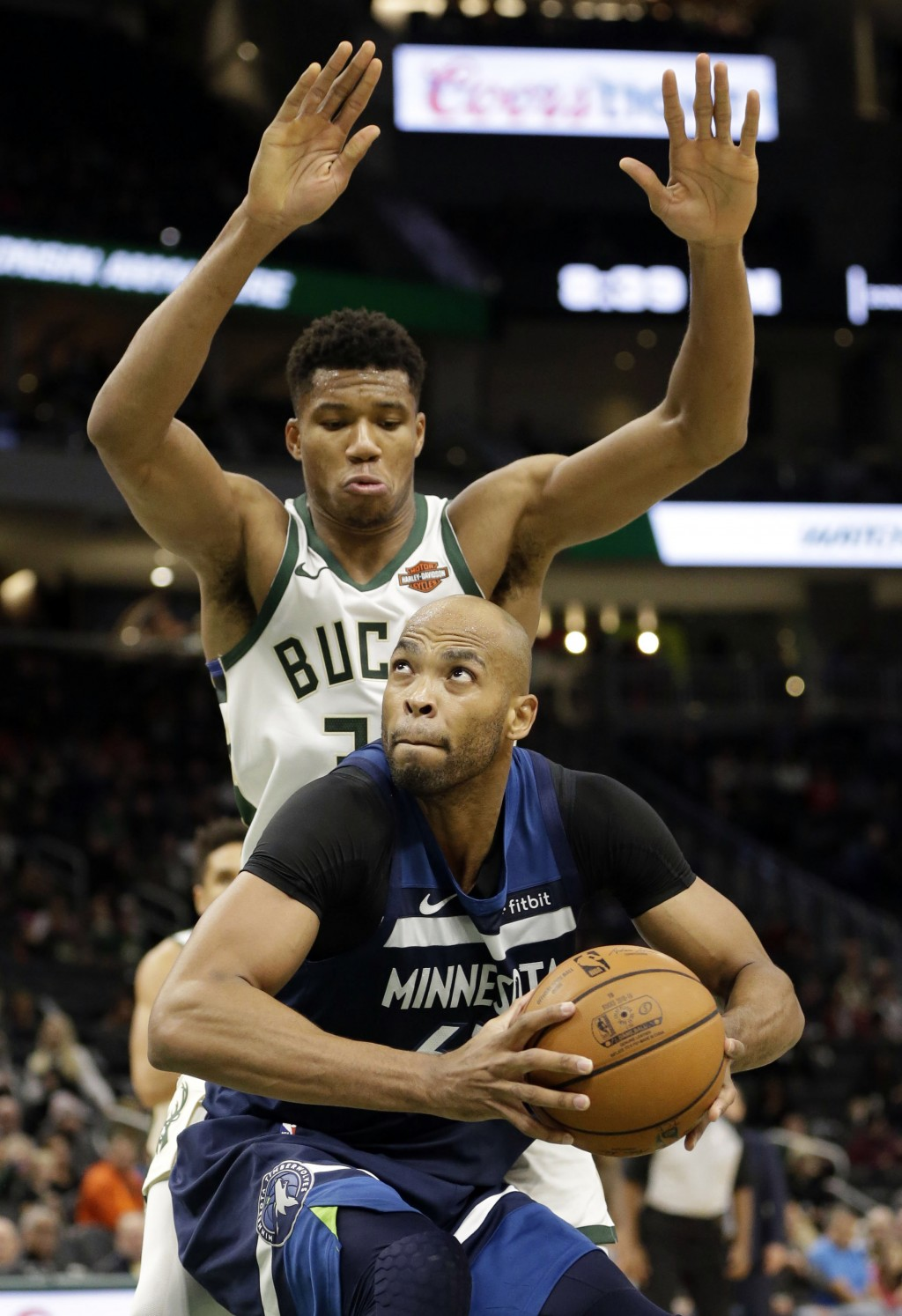 Milwaukee Bucks forward Giannis Antetokounmpo, top, defends as Minnesota Timberwolves forward Taj Gibson drives under the basket during the first half