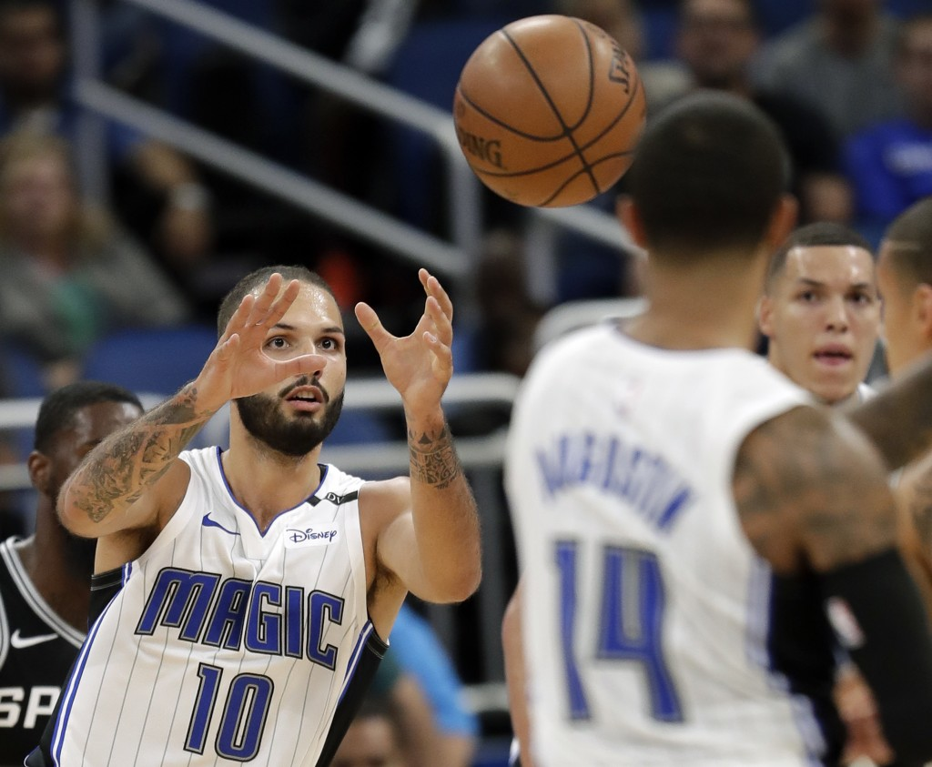 Orlando Magic's Evan Fournier (10) takes a pass from guard D.J. Augustin (14) during the second half of an NBA preseason basketball game against the S