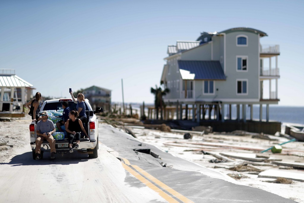 People drive along a damaged road in the aftermath of hurricane Michael in Mexico Beach, Fla., Friday, Oct. 12, 2018. (AP Photo/David Goldman)