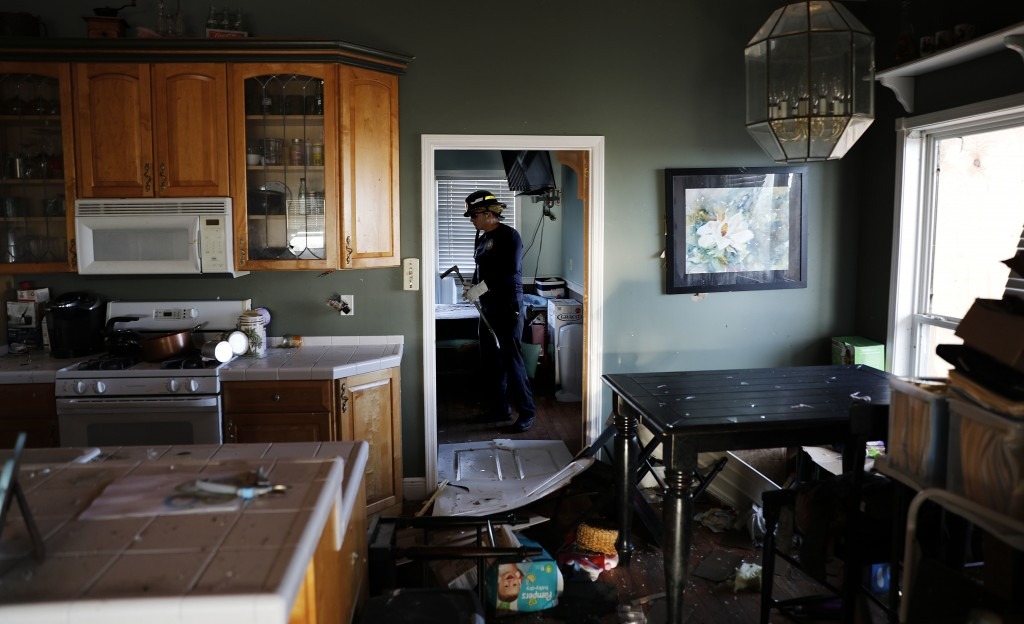A member of a South Florida urban search and rescue team checks a home for survivors of hurricane Michael in Mexico Beach, Fla., Friday, Oct. 12, 2018
