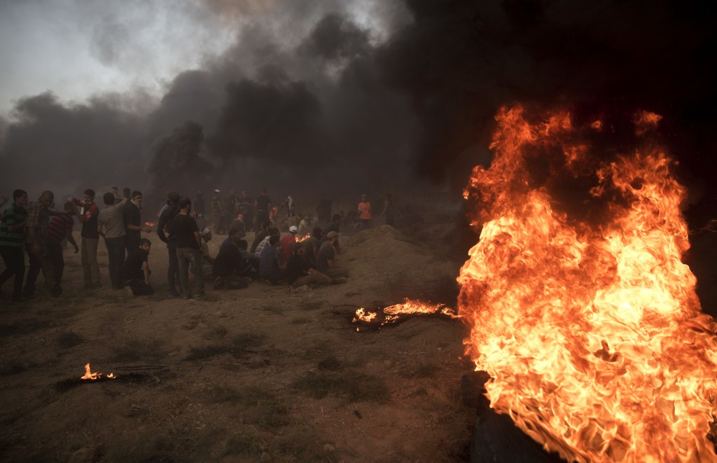 Black smoke from burning tires covers the sky over Palestinian protesters hurl stones toward Israeli troops during a protest at the Gaza Strip's borde