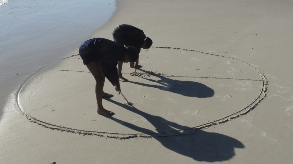 In this Tuesday, Aug. 21, 2018 photo, children from surrounding areas create calligraphy on a beach in Cape Town, South Africa. The Hangberg community