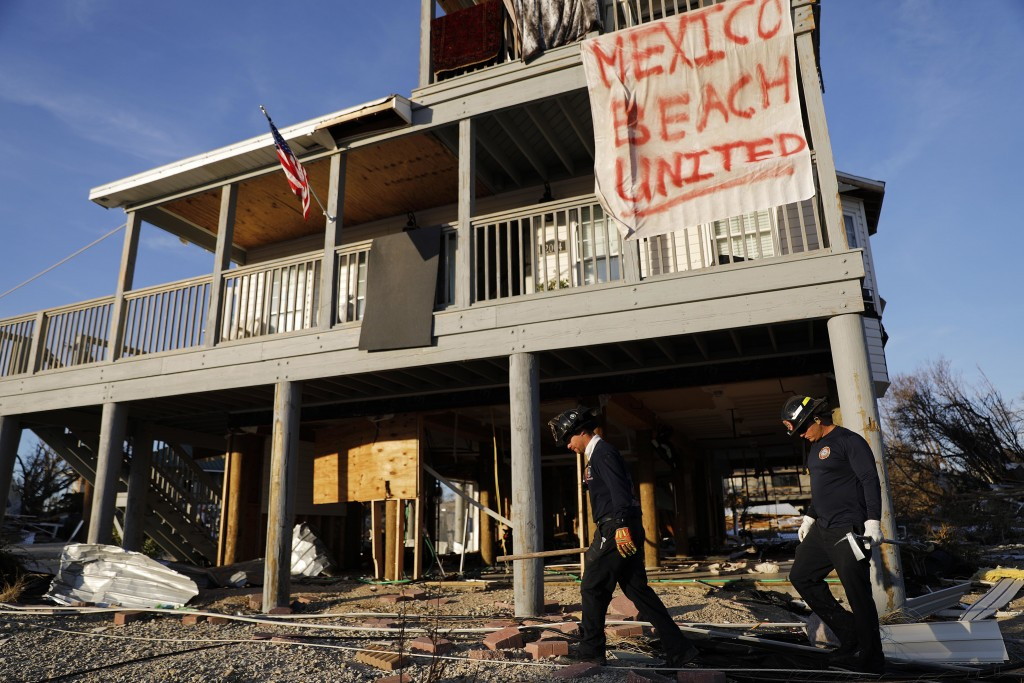 A banner hangs from a damaged home as a South Florida urban search and rescue team checks for survivors of hurricane Michael in Mexico Beach, Fla., Fr