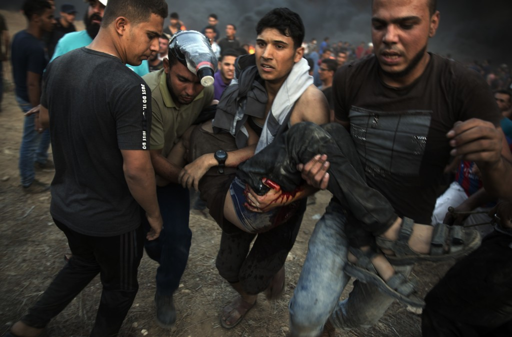 Palestinian protesters evacuate a wounded man shot by Israeli troops during a protest at the Gaza Strip's border with Israel, Friday, Oct. 12, 2018. (