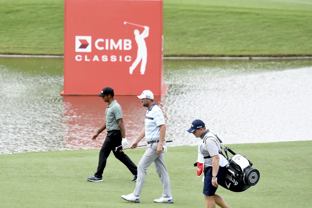 Shubhankar Sharma of India, left, and Marc Leishman of Australia walks on the fifth fairway during third round of the CIMB Classic golf tournament at