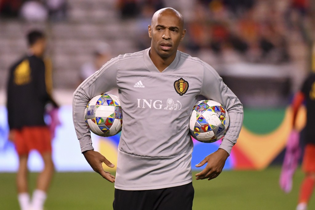 Belgium assistant coach Thierry Henry holds two balls during a warm up prior the UEFA Nations League soccer match between Belgium and Switzerland at t