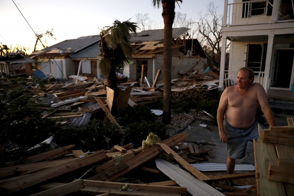 Dave Mullins looks out over the damage in front of his home, seen in background left, where he rode out hurricane Michael in Mexico Beach, Fla., Frida