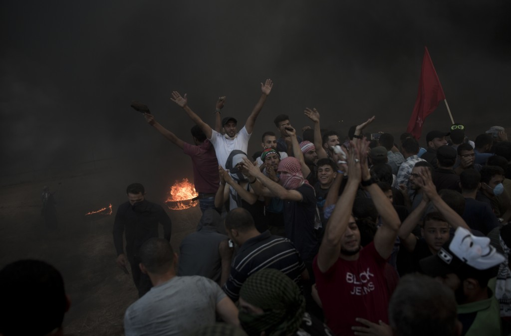 Palestinian protesters chant slogans during a protest at the Gaza Strip's border with Israel, Friday, Oct. 12, 2018. (AP Photo/Khalil Hamra)
