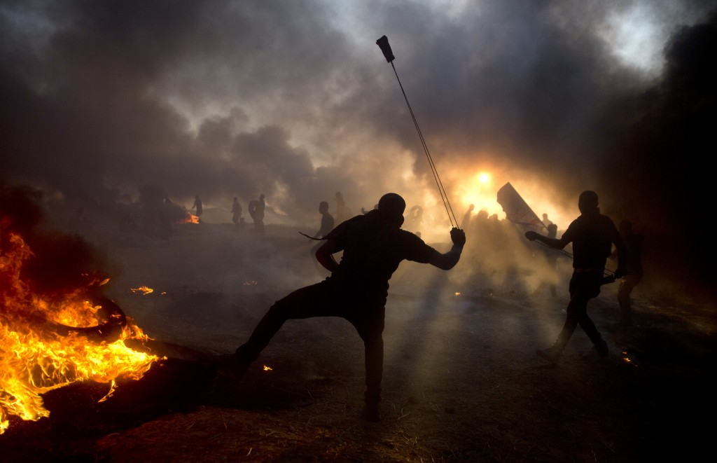 Black smoke from burning tires covers the sky as Palestinian protesters hurl stones toward Israeli troops during a protest at the Gaza Strip's border