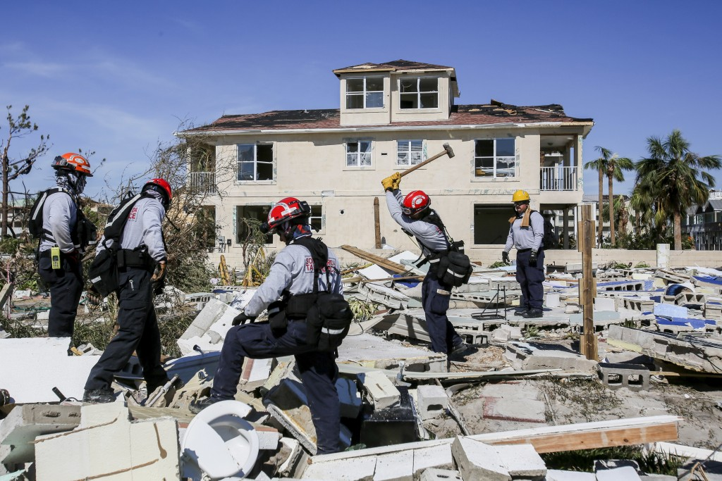 Members from South Florida Task Force search a flattened home destroyed by Hurricane Michael in Mexico Beach, Fla., Friday, Oct. 12, 2018. Mexico Beac