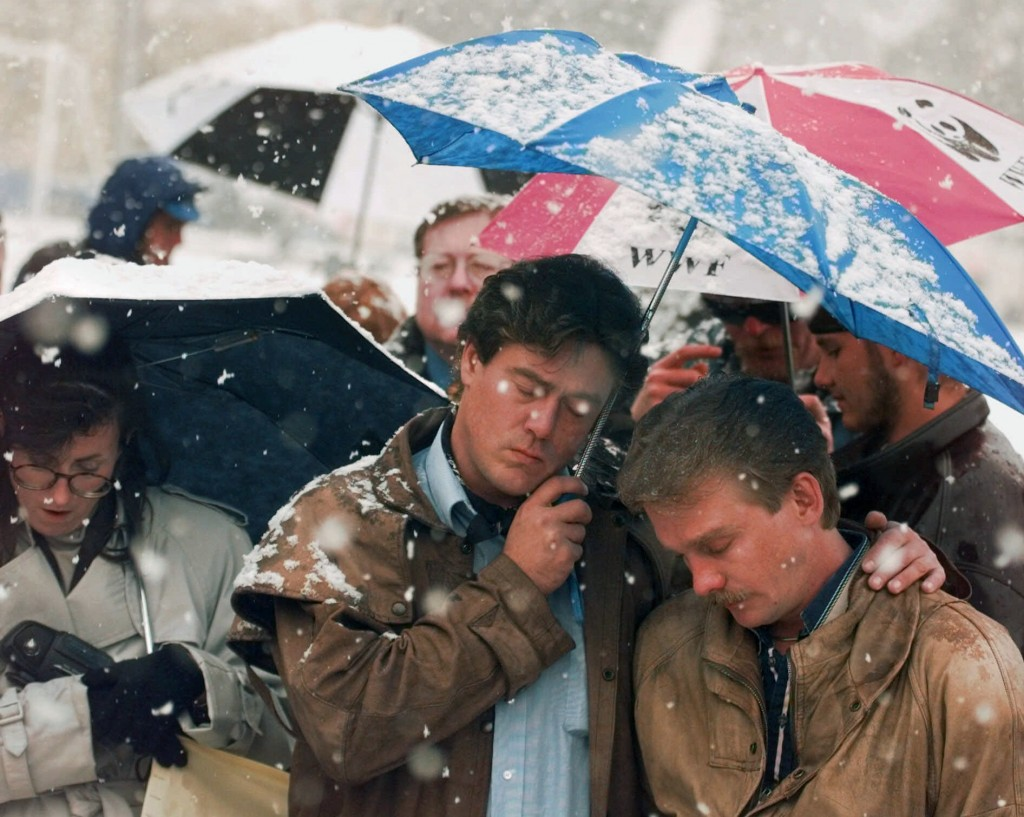 FILE - In this Oct. 16, 1998 file photo, Brian Harrington, right, and Chuck Beauchine pray with other mourners during the funeral of Matthew Shepard a