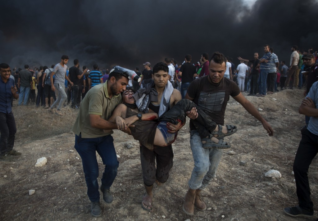 Palestinian protesters evacuate a wounded youth was shot by Israeli troops during a protest at the Gaza Strip's border with Israel, Friday, Oct. 12, 2