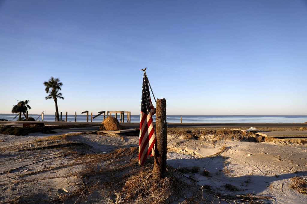 An American flag hangs from a broken palm tree along the water where homes were swept away by hurricane Michael in Mexico Beach, Fla., Saturday, Oct.