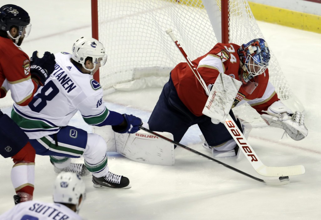 Florida Panthers goaltender James Reimer, right, stops the puck as Vancouver Canucks right wing Jake Virtanen attempts a shot during the first period