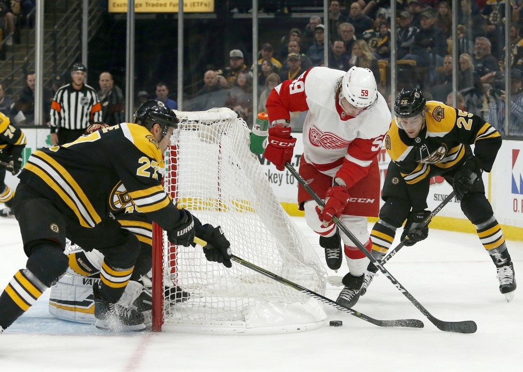Detroit Red Wings left wing Tyler Bertuzzi (59) tries to move the puck around the net as Boston Bruins players John Moore (27) and Brandon Carlo (25)