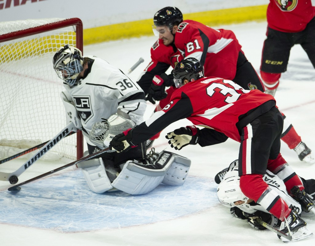 Ottawa Senators right wing Mark Stone (61) and centre Colin White (36) dive to push a puck across the goal line as Los Angeles Kings goaltender Jack C