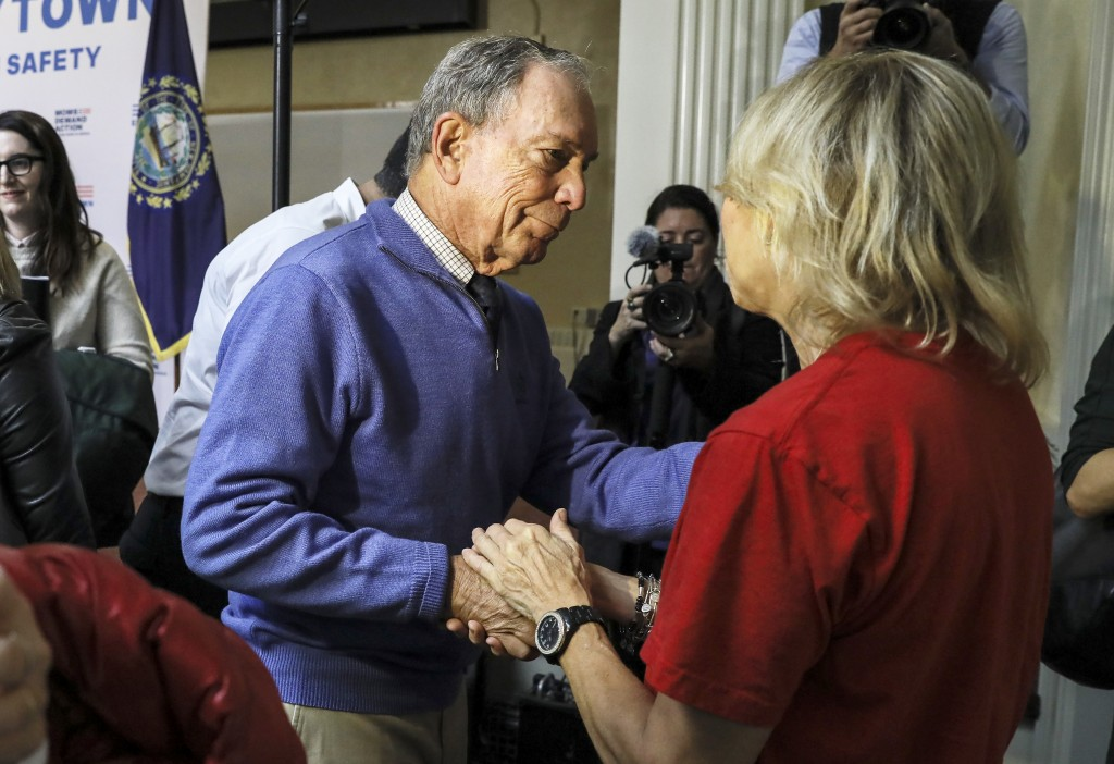Former New York Mayor Michael Bloomberg talks to a woman who lost her daughter to gun violence after speaking at a rally at City Hall in Nashua, N.H.