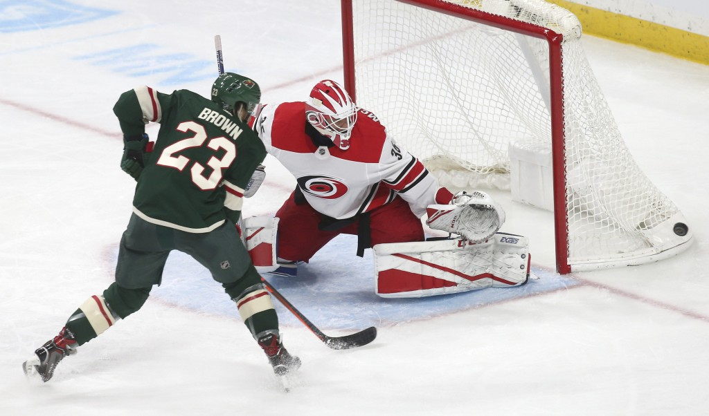 Carolina Hurricanes goalie Curtis McElhinney deflects a shot by Minnesota Wild's J.T. Brown during the second period of an NHL hockey game Saturday, O