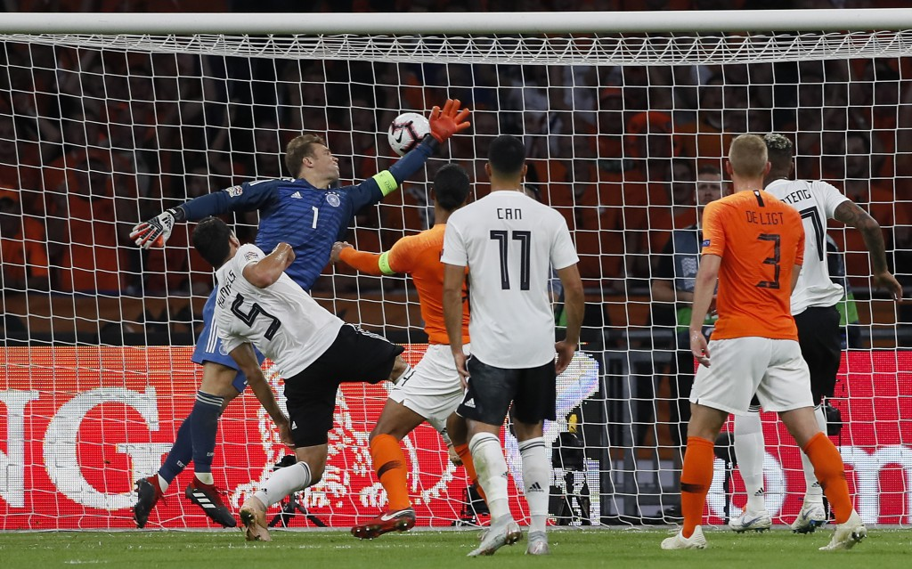 Netherland's Virgil Van Dijk, center, heads the opening goal against Germany's keeper Manuel Neuer during the UEFA Nations League soccer match between