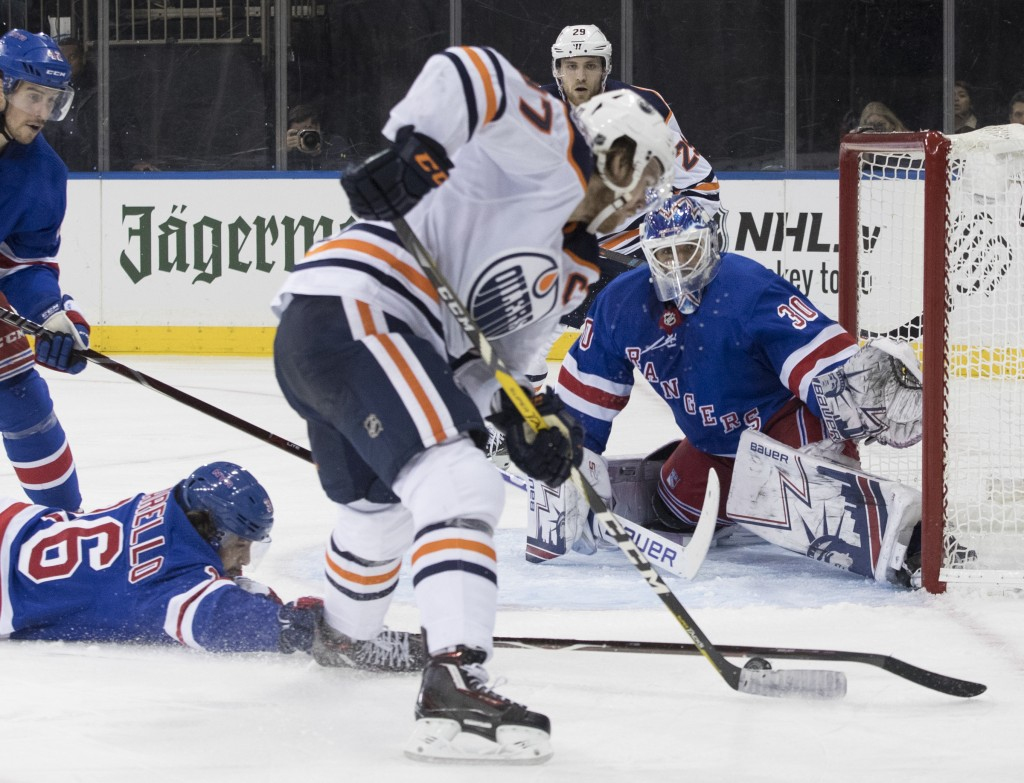Edmonton Oilers center Connor McDavid (97) shoots the puck to score past New York Rangers right wing Mats Zuccarello (36) and goaltender Henrik Lundqv