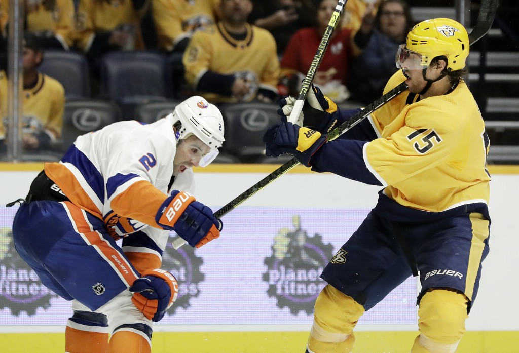 New York Islanders defenseman Nick Leddy (2) hits Nashville Predators right wing Craig Smith (15) with his stick as they chase the puck in the second