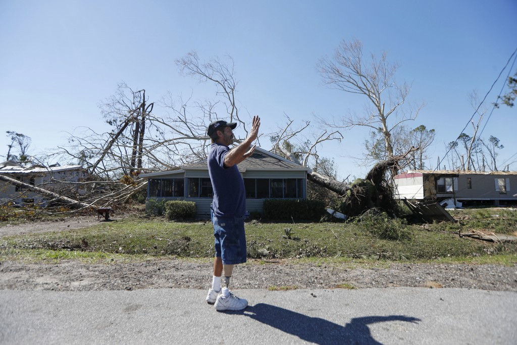 In this Oct. 13, 2018 photo, Clinton Moseley who lives with his mother, stands in front of her home after a tree fell on the home during Hurricane Mic...
