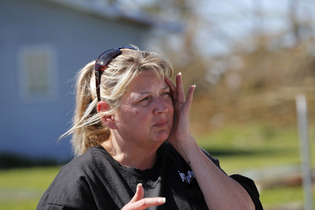 In this Oct. 13, 2018 photo, Pam Rudd reacts as she helps her mother-in-law remove possessions from her damaged home in the aftermath of Hurricane Mic...