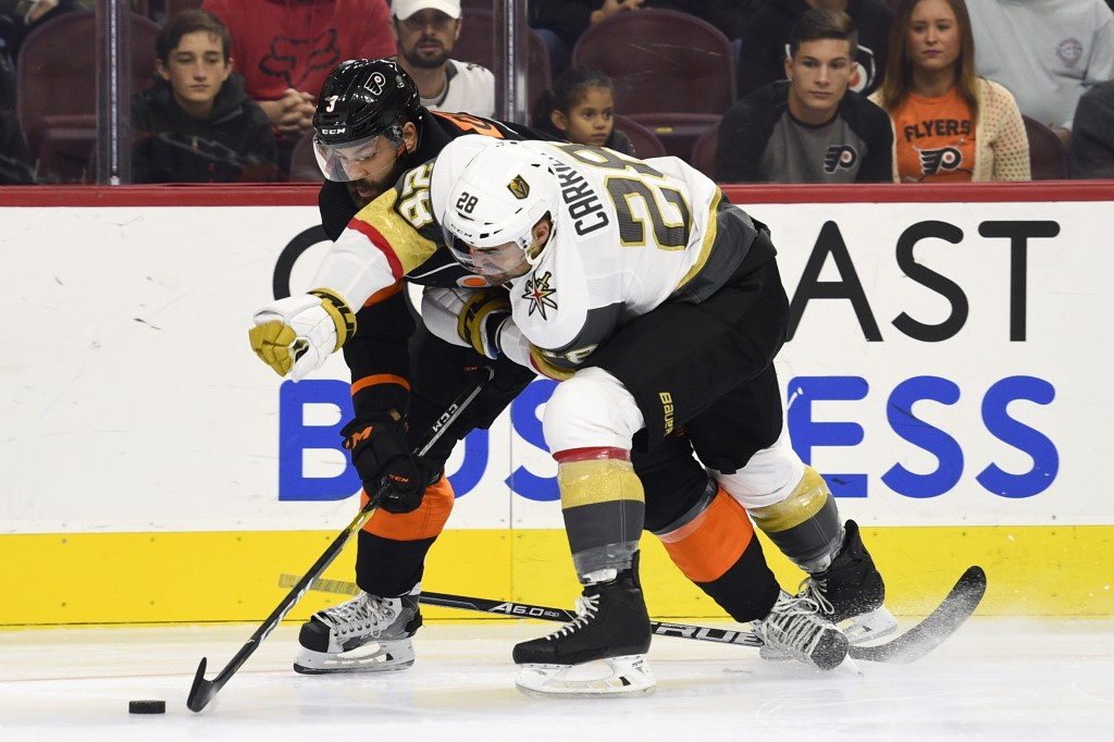 Vegas Golden Knights' William Carrier, right, holds onto Philadelphia Flyers' Radko Gudas as they battle for the puck during the first period of an NH