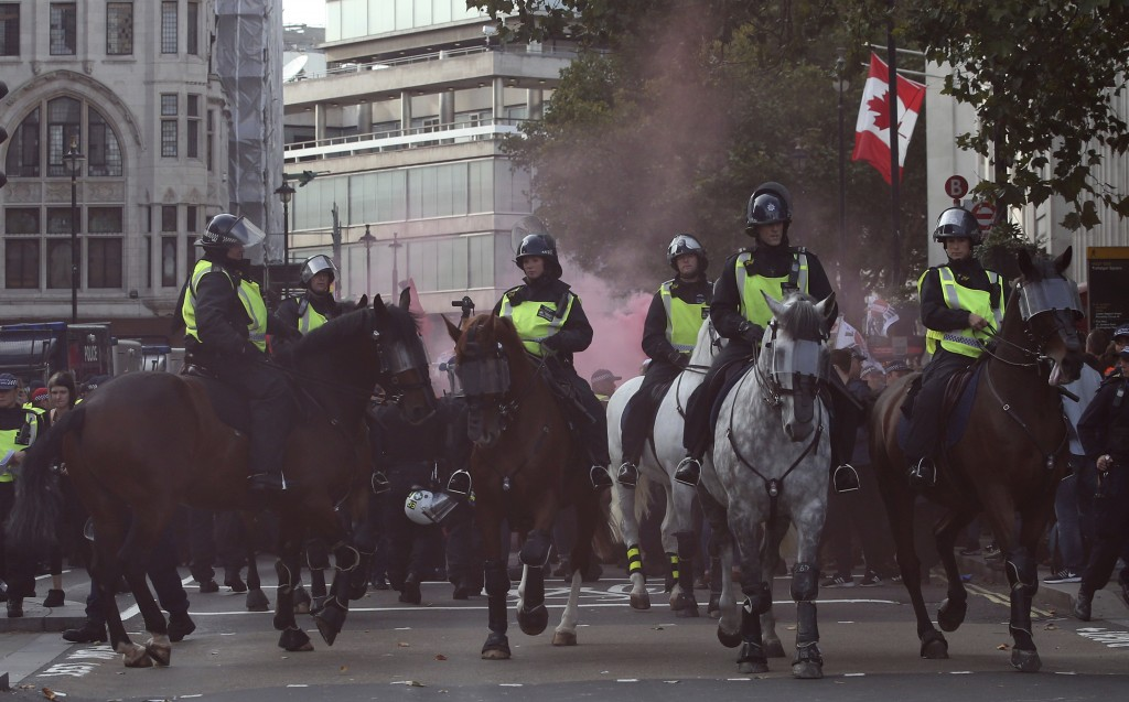 Mounted police horses react to a flare going off during an anti-fascist demonstration held in protest against a rival march by the Football Lads Allia
