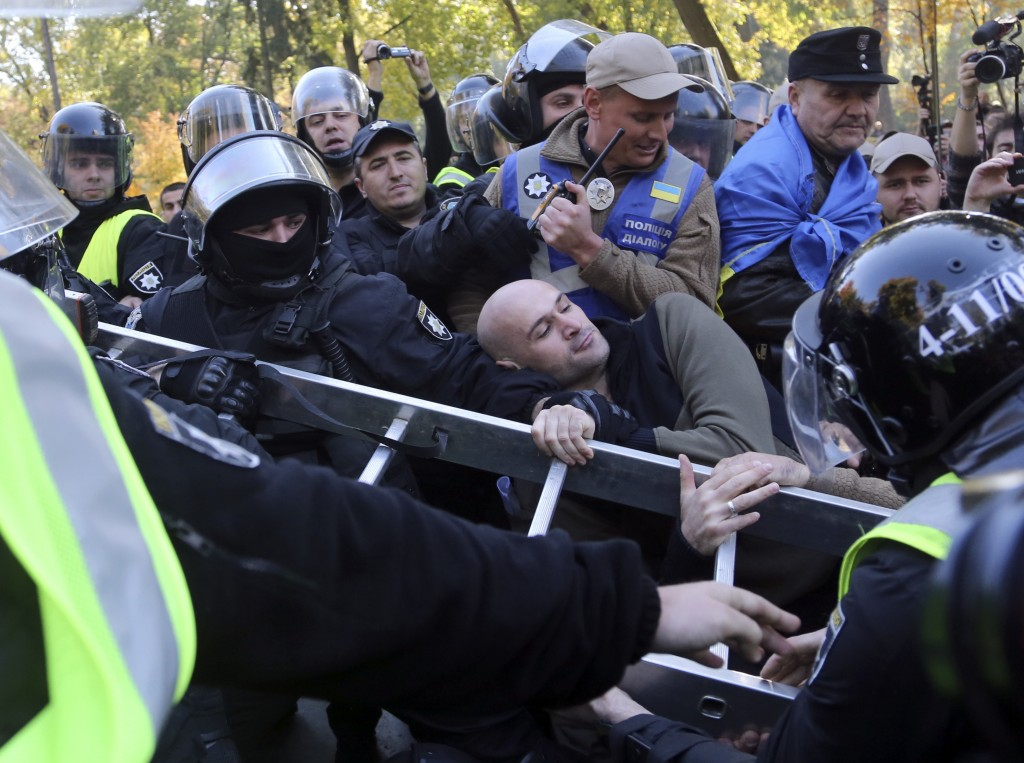 Right wing activists scuffle with riot police as they pull a ladder in an attempt to destroy a Soviet-era monument during a protest near the parliamen