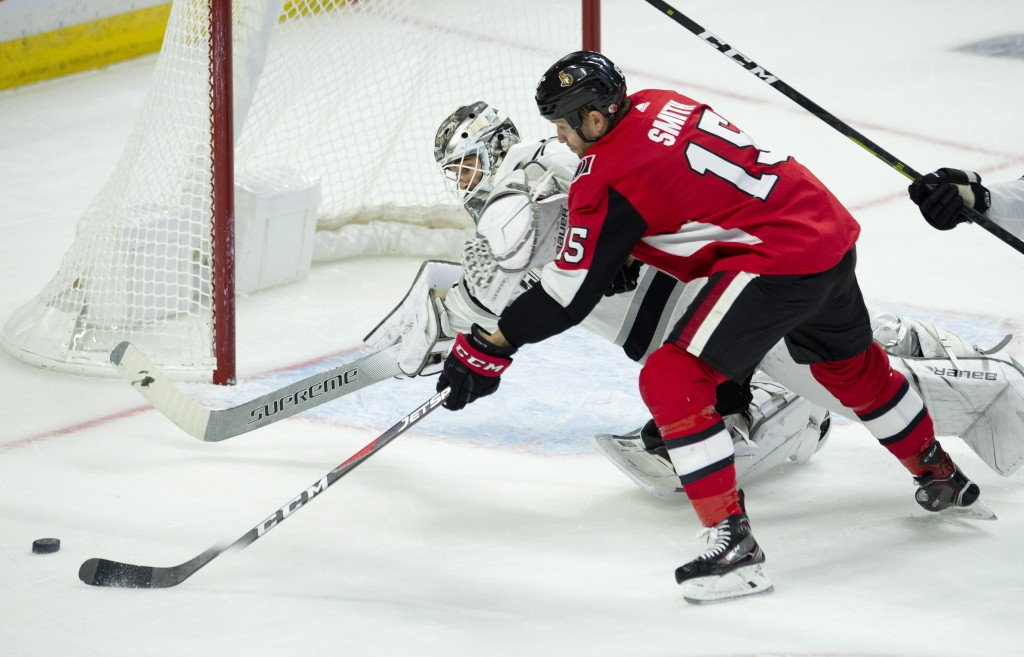 Los Angeles Kings goaltender Peter Budaj dives to block a shot from Ottawa Senators left wing Zack Smith (15) during third period NHL hockey action in