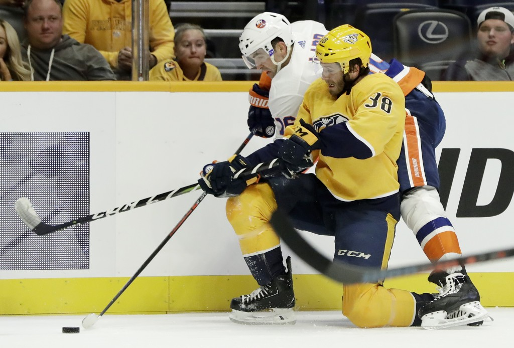 Nashville Predators right wing Ryan Hartman (38) battles New York Islanders left wing Andrew Ladd (16) for the puck during the first period of an NHL