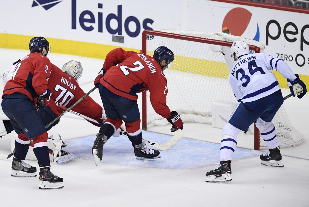 Toronto Maple Leafs center Auston Matthews (34) scores a goal against Washington Capitals defenseman Dmitry Orlov (9), of Russia, Matt Niskanen (2) an