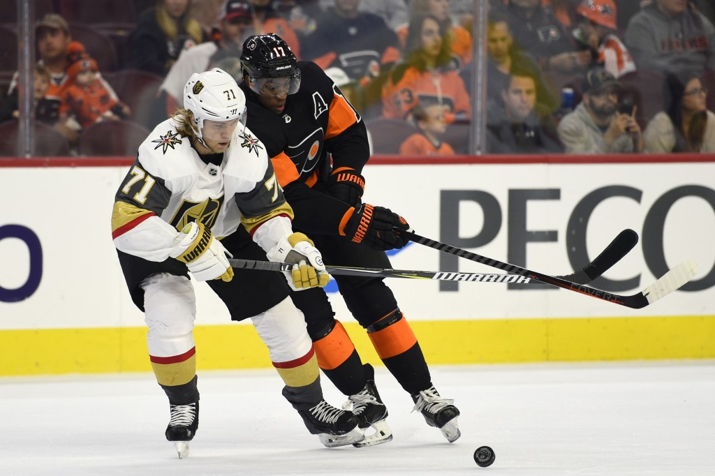 Vegas Golden Knights' William Karlsson, left, and Philadelphia Flyers' Wayne Simmonds battle for a loose puck during the first period of an NHL hockey