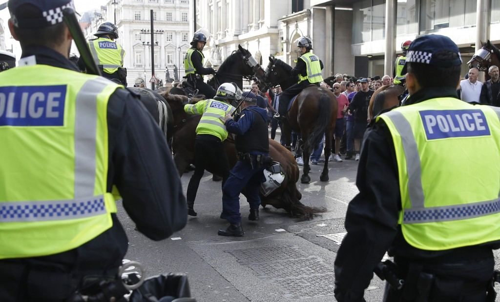 A police officer is dismounted as he helps stop a breakaway from the main Football Lads Alliance march, as they attempt to get close to a rival anti-f