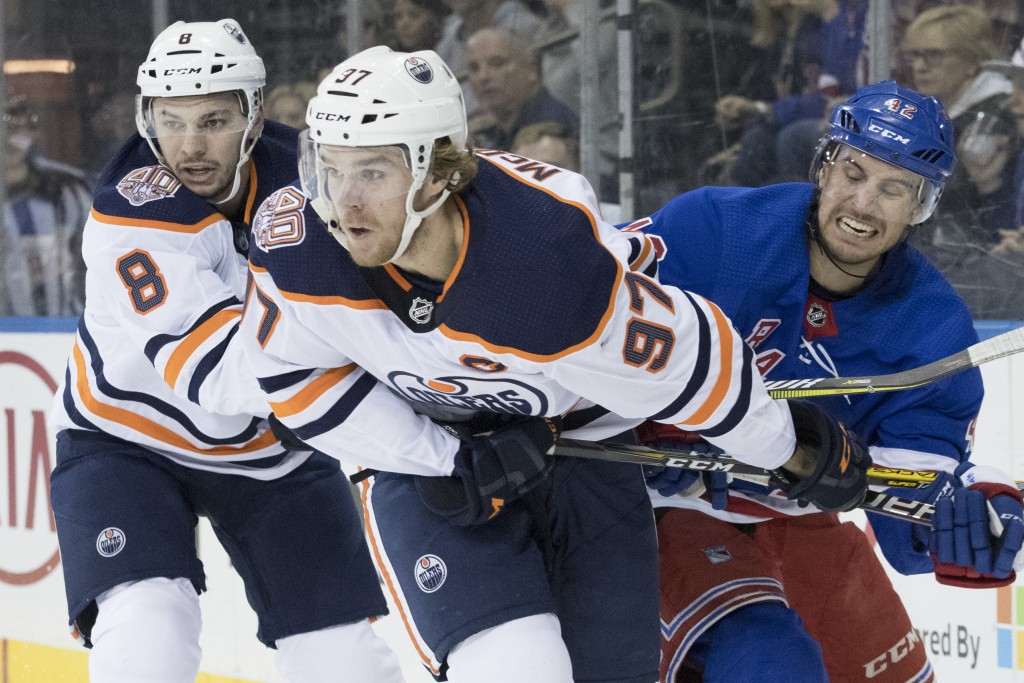 Edmonton Oilers right wing Ty Rattie (8), center Connor McDavid (97) and New York Rangers defenseman Brendan Smith (42) vie for a loose puck during th