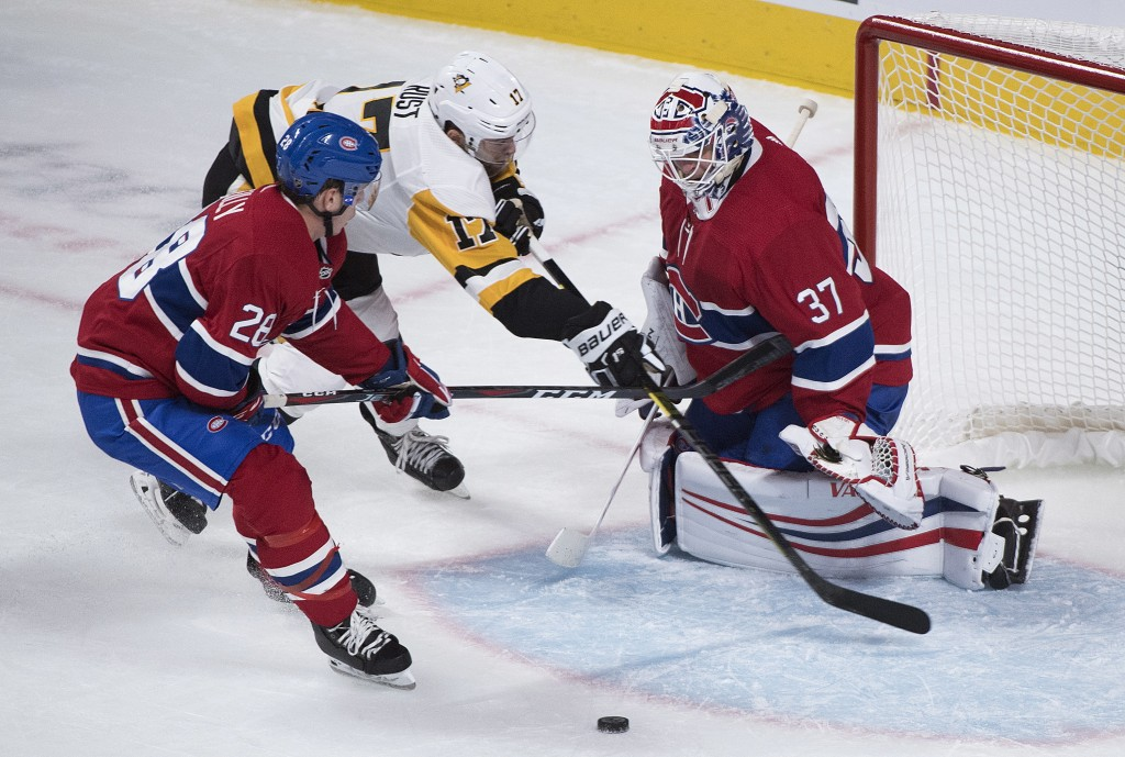 Pittsburgh Penguins' Bryan Rust (17) moves in on Montreal Canadiens goaltender Antti Niemi as Canadiens' Noah Juulsen defends during the third period