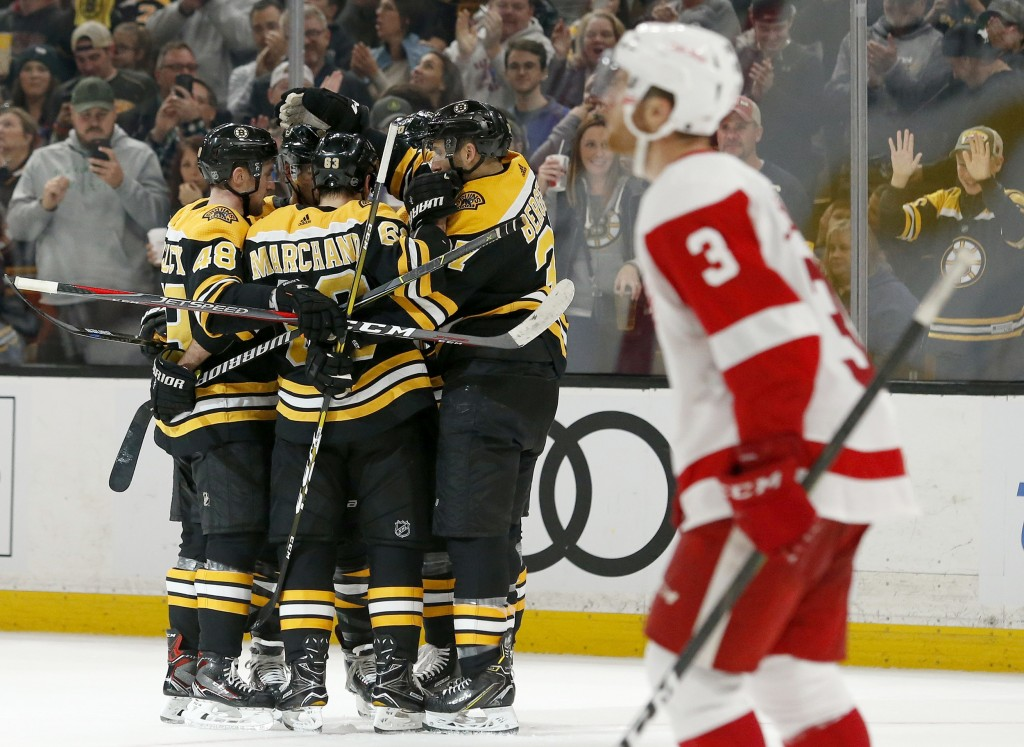 Boston Bruins players surround David Pastrnak after he scored as Detroit Red Wings defenseman Nick Jensen (3) looks up for the replay during the secon