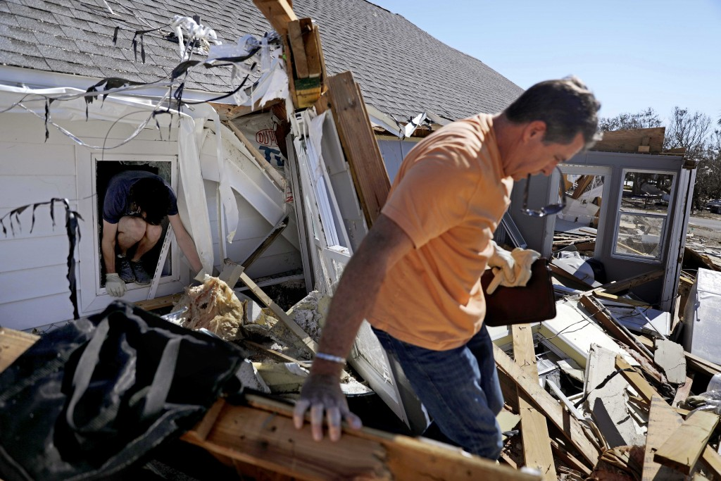 Joshua Kerigan, 19, left, crawls out of a window after retrieving some belongings with his father Jack Kerigan from their damaged house in the afterma