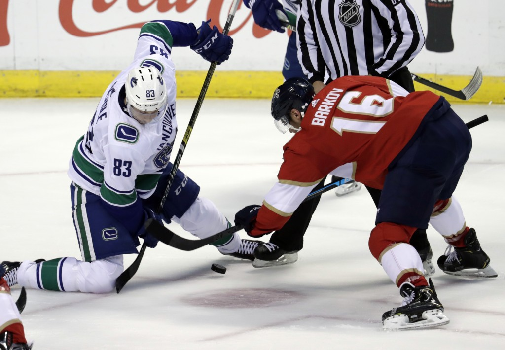 Vancouver Canucks center Jay Beagle (83) and Florida Panthers center Aleksander Barkov (16) go for the puck during the first period of an NHL hockey g