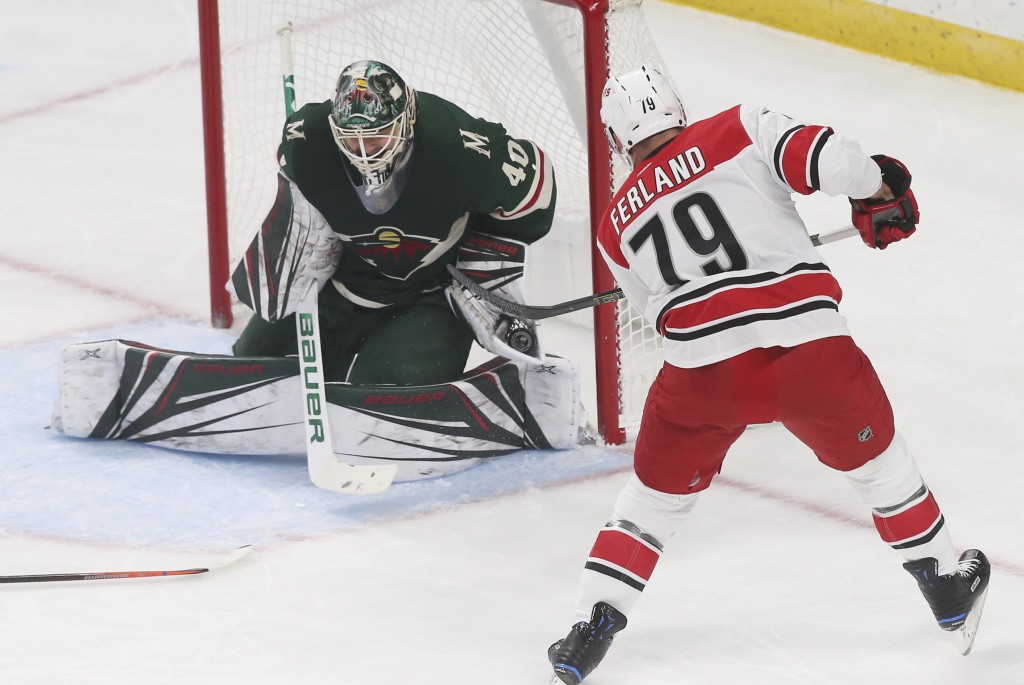 Minnesota Wild goalie Devan Dubnyk makes a glove save on a shot by Carolina Hurricanes' Micheal Ferland during the first period of an NHL hockey game