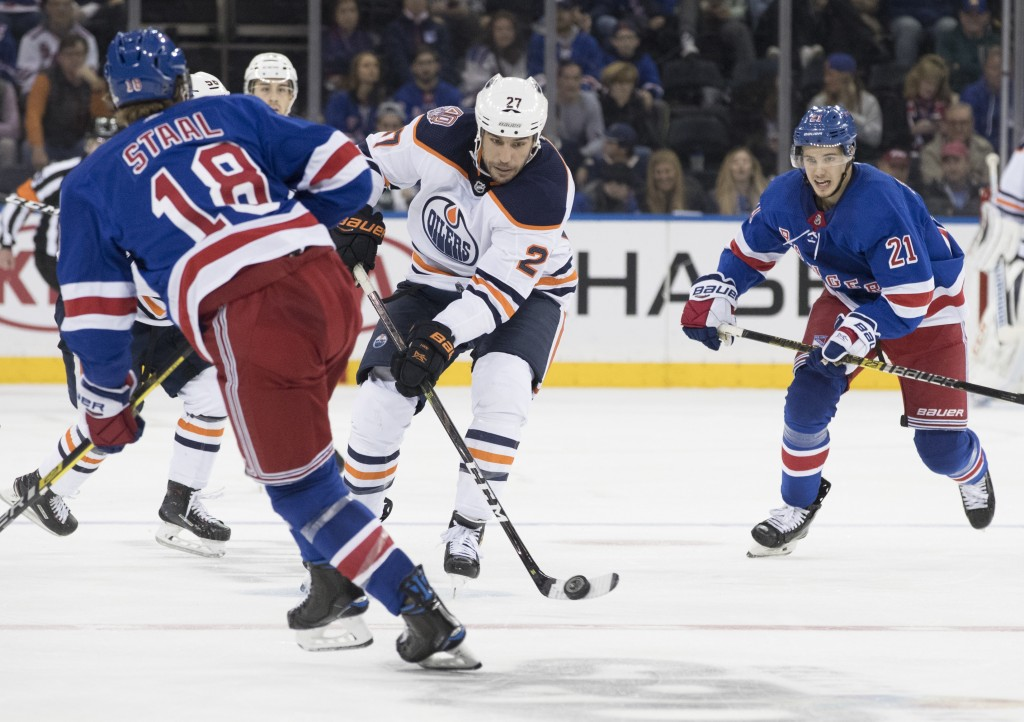 Edmonton Oilers left wing Milan Lucic (27) plays the puck against New York Rangers defenseman Marc Staal (18) during the third period of an NHL hockey