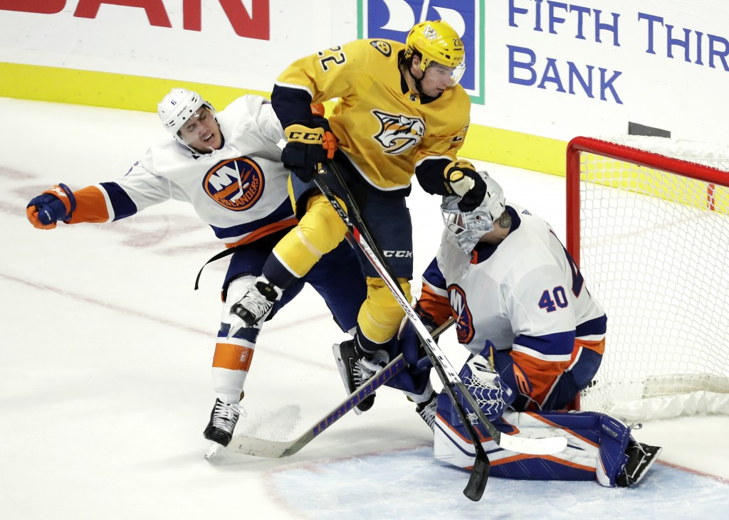 Nashville Predators left wing Kevin Fiala (22), of Switzerland, collides with New York Islanders defenseman Ryan Pulock, left, and goaltender Robin Le