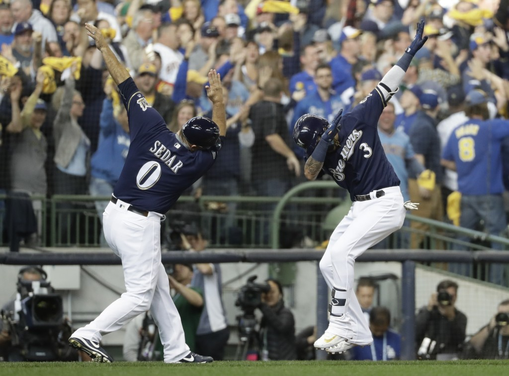 Milwaukee Brewers' Orlando Arcia celebrates his home run with third base coach Ed Sedar during the fifth inning of Game 2 of the National League Champ